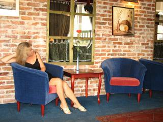 фойе гостиницы, декоративное окно, в креслах - девушка, она смотрит на картину